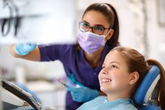 Child in dental chair with female dentist looking at dental foot. Female child in dental chair with female dentist looking at dental footage stock photo