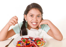 Female child eating dish full of candy in sugar excess and sweet nutrition abuse Stock Image