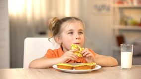 Female child eating tasty donut, milk glass on table, sweet snack, nutrition stock image