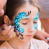 Female child face painting, making butterfly process. Child animator, artist`s hand draws face art to little girl. Blue butterfly painting. Children birthday royalty free stock photos
