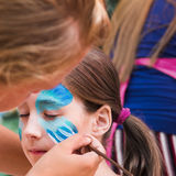 Female child face painting, making butterfly process. Child animator, artist`s hand draws face art to little girl. Blue butterfly painting. Children birthday royalty free stock photo