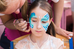 Female child face painting, making butterfly process stock images