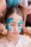 Female child face painting, making butterfly process. Child animator, artist`s hand draws face art to little girl. Blue butterfly painting. Vertical orientation stock photos