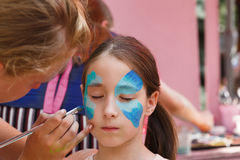 Female child face painting, making butterfly process. Child animator, artist's hand draws face painting to little girl. Child with funny face painting. Painter stock photography