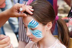 Female child face painting, making butterfly process. Child animator, artist's hand draws face painting to little girl. Child with funny face painting. Painter stock image