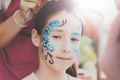 Female child face painting, making butterfly process stock image