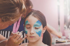 Female child face painting, making butterfly process. Child animator, artist's hand draws face painting to little girl. Child with funny face painting. Painter stock photos