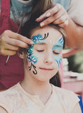 Female child face painting, making butterfly process. Child animator, artist's hand draws face painting to little girl. Child with funny face painting. Painter royalty free stock image