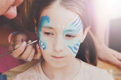 Female child face painting, making butterfly process. Child animator, artist's hand draws face painting to little girl. Child with funny face painting. Painter royalty free stock images