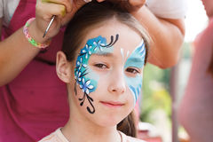 Female child face painting, making butterfly process. Child animator, artist's hand draws face painting to little girl. Child with funny face painting. Painter stock images