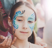 Female child face painting, making butterfly process. Child animator, artist`s hand draws face painting to little girl. Child with funny face painting. Painter stock photos