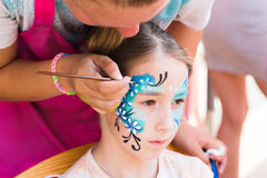 Female child face painting, making butterfly process. Face art for little girl. Blue butterfly painting. Children birthday party entertainment, artist making stock photo