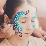 Female child face painting, making butterfly process. Child face art made to little girl. Blue butterfly painting. Children birthday party entertainment stock image