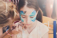 Female child face painting, making butterfly process royalty free stock images