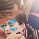 Female child face painting, making butterfly process. Child face painting made to little girl. Blue butterfly. Children birthday party entertainment royalty free stock image