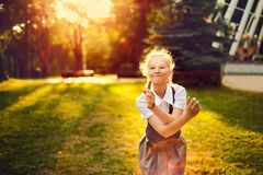 Schoolgirl in uniform with pigtails joyful dancing at sunset i royalty free stock photography
