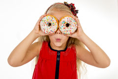 Female child with long blonde hair and red dress playing with two sugar donut with toppings putting them like eyes Royalty Free Stock Image
