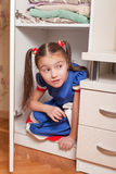 Female child looks out of the closet. Royalty Free Stock Image