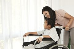 Female child patient in wheelchair. Young female child patient in wheelchair sitting at hospital with Asian mom stock photography