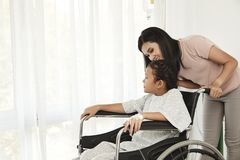 Female child patient in wheelchair. Young female child patient in wheelchair sitting at hospital with Asian mom royalty free stock images
