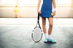 Female child playing tennis indoors Stock Photo