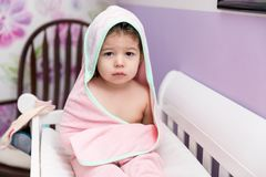 Female Child Resting In Crib After Bath. Portrait of little girl wrapped in hooded towel in crib at home royalty free stock photos