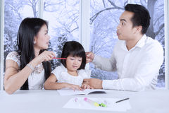 Female child studying while her parents arguing. Portrait of a crying female child while studying with her parents quarreling at home Stock Photos