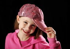 Female child wearing pink sparkly baseball cap. Young girl wearing a pink sequin baseball cap smiling, on black background Stock Photography