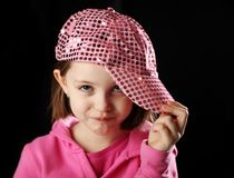 Female child wearing sparkly pink baseball cap. Young girl wearing a pink sequin baseball cap rolling her eyes with attitude, on black background Royalty Free Stock Image
