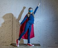 Female child 7 or 8 years old young girl performing happy and excited posing wearing cap and mask in super hero fantasy costume lo. Oking playful in studio royalty free stock photo
