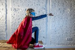 Female child 7 or 8 years old young girl performing happy and excited posing wearing cap and mask in super hero fantasy costume lo. Oking playful in studio stock images