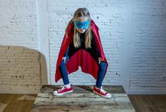 Female child 7 or 8 years old young girl performing happy and excited posing wearing cap and mask in super hero fantasy costume lo. Oking playful in studio royalty free stock photos