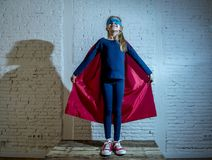 Female child 7 or 8 years old young girl performing happy and excited posing wearing cap and mask in super hero fantasy costume lo. Oking playful in studio royalty free stock image