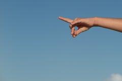 Female or children pointing finger under blue sky Stock Photo