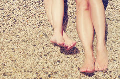 Female and children's feet on a beach against the sea in a summer sunny day. Royalty Free Stock Image