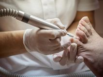 Female chiropodist working on a senior clients feet. Female chiropodist at work on a senior clients feet stock photos