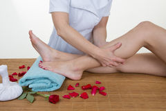 Female chiropractor checking patients leg on massage table royalty free stock photos