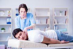 The female chiropractor doctor massaging male patient. Female chiropractor doctor massaging male patient Royalty Free Stock Photo