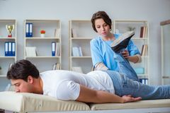 The female chiropractor doctor massaging male patient. Female chiropractor doctor massaging male patient Royalty Free Stock Photography