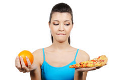 Female choose between pizza and orange Royalty Free Stock Photos