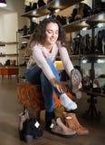 Female choosing winter women shoes. Happy female choosing winter woman shoes in a shoe store stock image