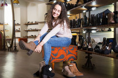 Female choosing winter women shoes Royalty Free Stock Images