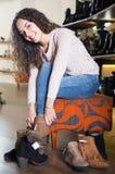 Female choosing winter women shoes. Female choosing winter woman shoes in a shoe store royalty free stock images