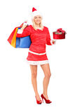 Female in christmas costume holding gift and bags Royalty Free Stock Photo