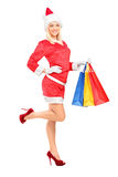 Female in christmas costume holding shopping bags. Full length portrait of a female in christmas costume holding shopping bags  on white background Stock Photo