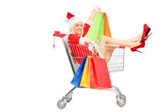 Female in christmas costume into a push cart Stock Images