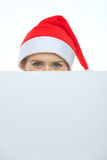 Female in Christmas hat hiding behind billboard. Female in Christmas hat hiding behind blank billboard Royalty Free Stock Photos