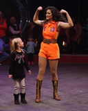 Female circus performer with young girl. Female circus performer doing body builder pose as young girl watches Royalty Free Stock Images