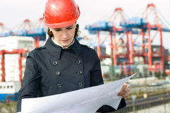 Female civil engineer. Wearing helm and checking the drawings in front of container terminal in harbor stock photography