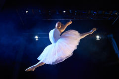 Female classic dancer jumping mid air during ballet. Arts and entertainment in theatre with female classic dancer in tutu, jumping high on stage during royalty free stock photos